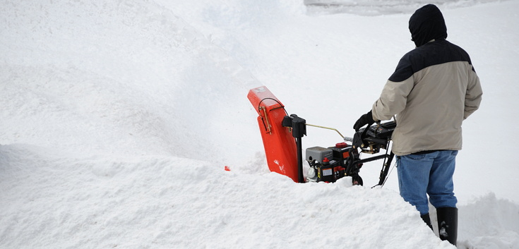 man clearing deep snow drifts with a machine